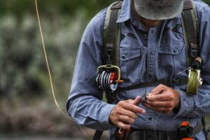 A fly fishing guide uses a pocket knife to cut fishing line near CM Ranch in Dubois, WY | Wyoming dude ranch vacations