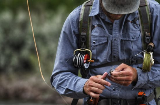 A fly fishing guide uses a pocket knife to cut fishing line near CM Ranch in Dubois, WY   Wyoming dude ranch vacations