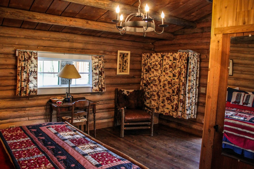 Bed, dresser, tables and chairs in Dining Cabin | Wyoming Guest Ranches | CM Ranch
