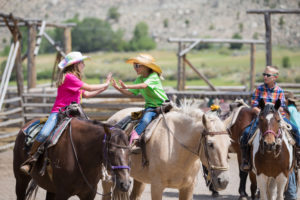 Two girls share a double high-five on horseback at CM Ranch in Dubois, WY | Dude Ranch Wyoming Family