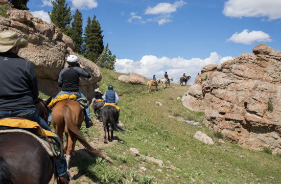 Riders on horseback ride a trail through rocky outcroppings near CM Ranch in Dubois, WY