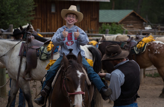 A boy on horseback gives a double thumbs-up at CM Ranch in Dubois, WY | Wyoming dude ranch
