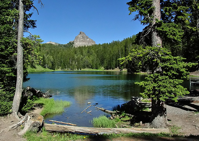 A mountain top peeks above the treeline at an alpine lake in Wyoming