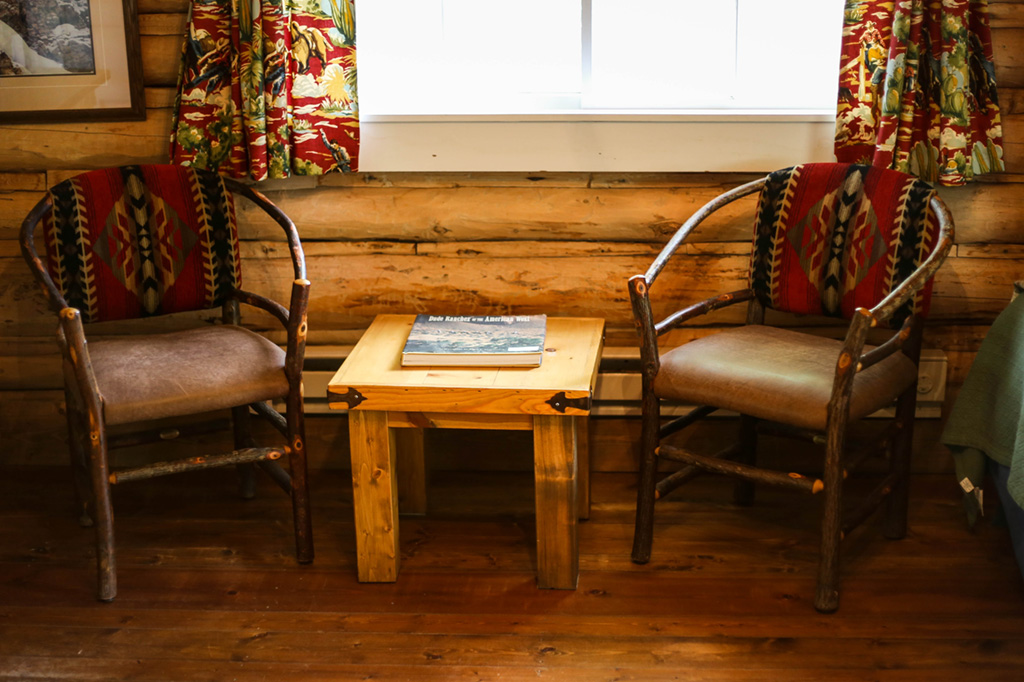 Two chairs and a side table at Dining Cabin 6 | Dubois Wyoming Lodging | CM Ranch
