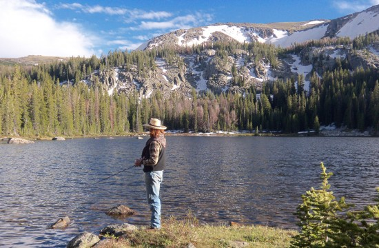 A person stands fishing along the bank of a river near CM Ranch in Dubois, WY | Wyoming dude ranch