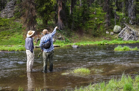 A fly fishing guide instructs a guest near CM Ranch in Dubois, WY | Wyoming dude ranch