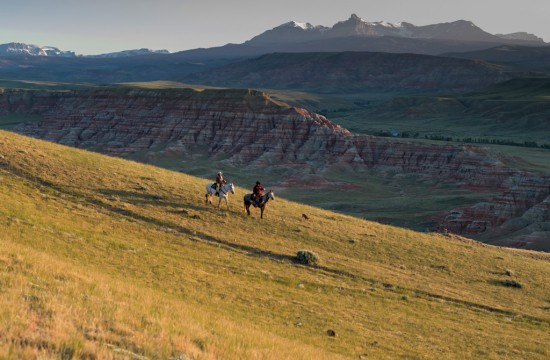 Two riders on horseback in an expansive landscape at sunset at CM Ranch in Dubois, WY | cabins in Dubois Wyoming