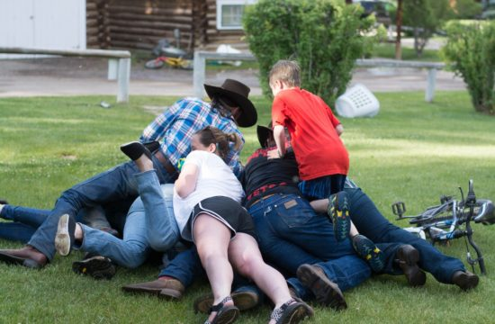 A family of ranchers pile up on each other during a playful moment